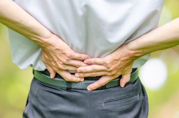 Hernia discal lumbar manos en espalda
