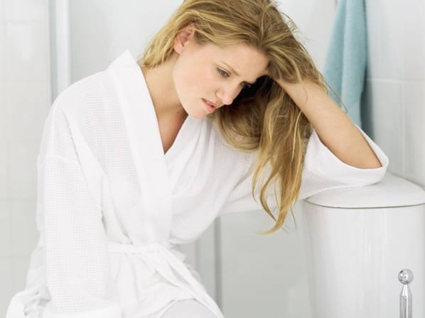 Young woman in a bathrobe sitting holding her head